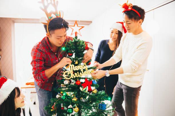 freunde schmücken weihnachtsbaum - weihnachten japan stock-fotos und bilder