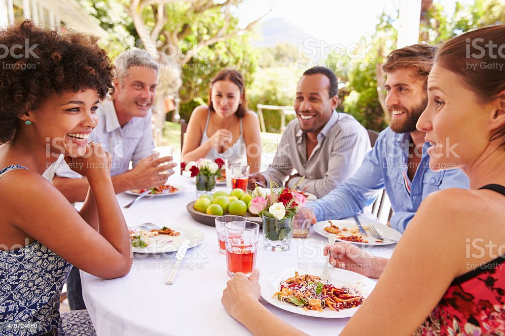 Friends dining together at a table in a garden stock photo