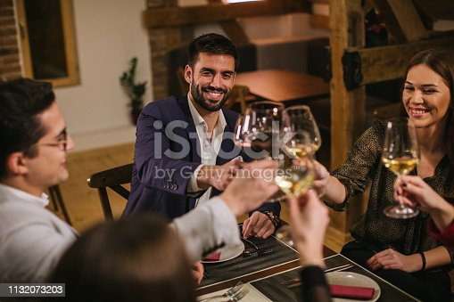 Group of cheerful friends sitting in luxury restaurant, toasting with wine, high angle view