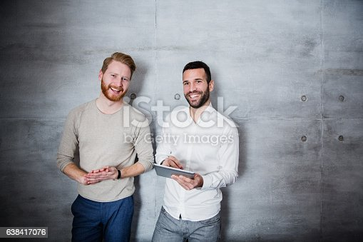 Friends standing against the wall with tablet and discussing, looking at camera