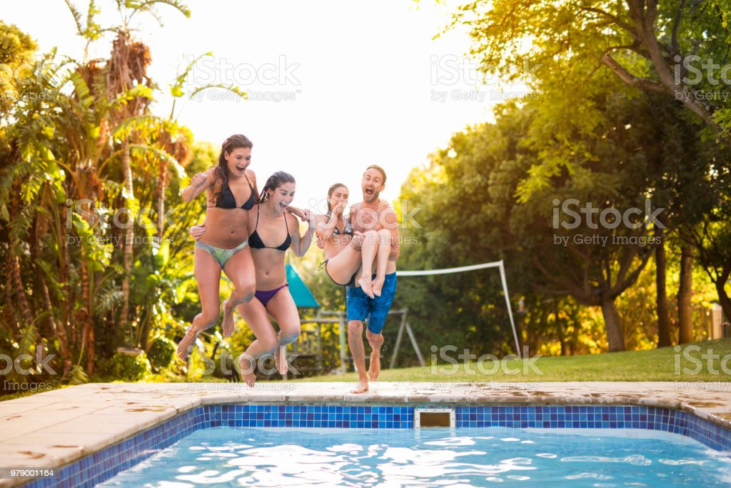 Friends diving in swimming pool at resort in garden party. Excited...