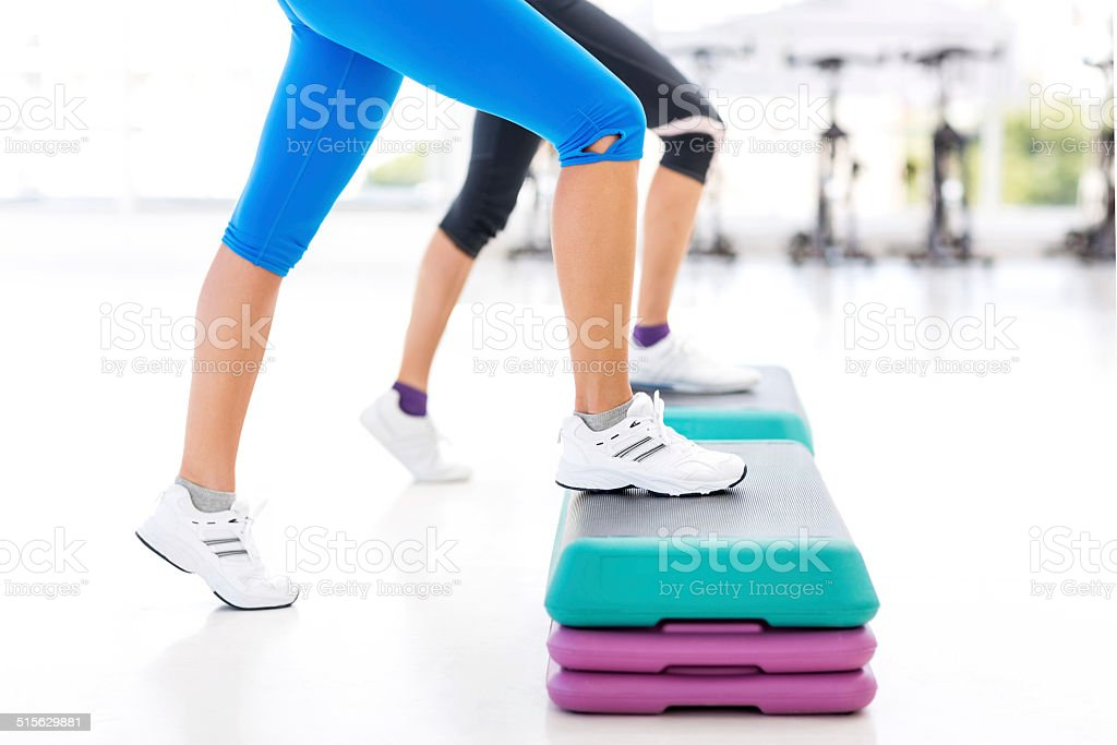 Friends Doing Aerobics Exercise On Steps In Health Club Stock
