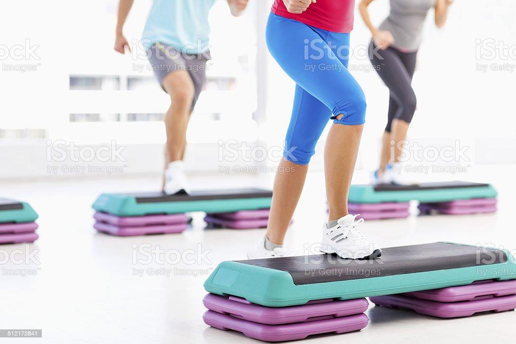 Amigos fazendo uso de Aeróbica Step na academia de ginástica - foto de acervo