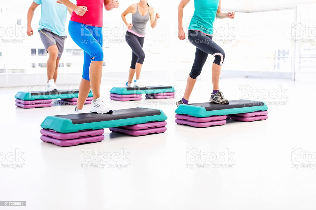 Friends Doing Aerobics Using Stair Stepper In Health Club stock photo