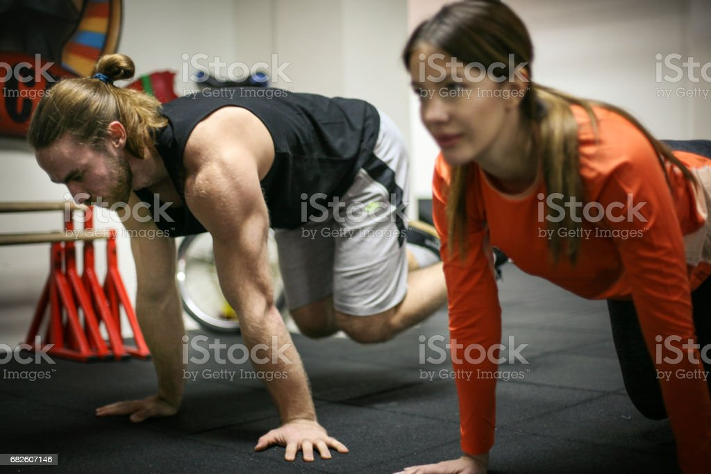 Friends doing exercises in a gym with straps. Two friends in the gym. stock photo