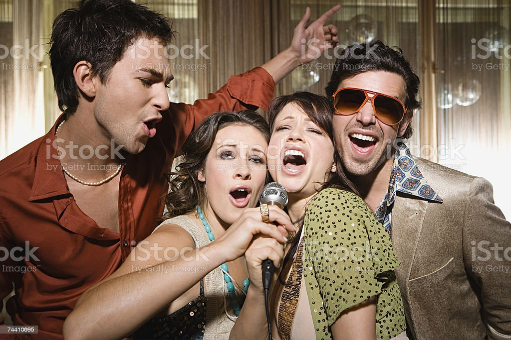 Friends doing karaoke stock photo