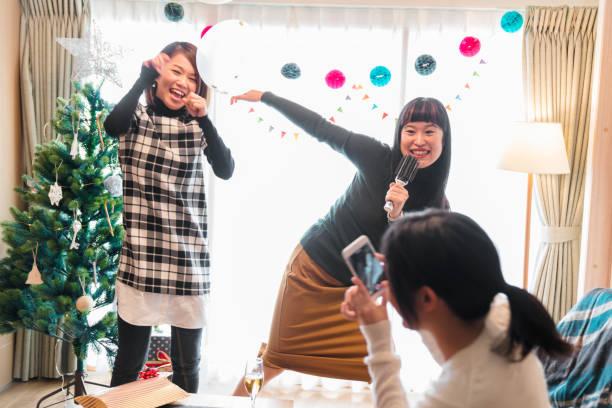 freunde, die gemeinsam karaoke zu hause zu weihnachten - weihnachten japan stock-fotos und bilder