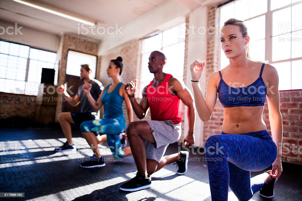 Friends doing lunges during a workout in the gym stock photo