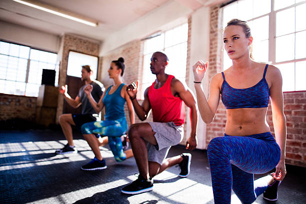 friends doing lunges during a workout in the gym - aerobics stock photos and pictures
