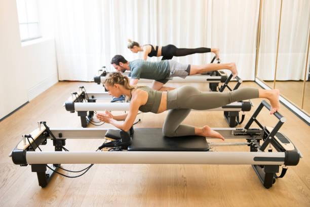 friends doing pilates kneeling glutes exercises - metodo pilates foto e immagini stock