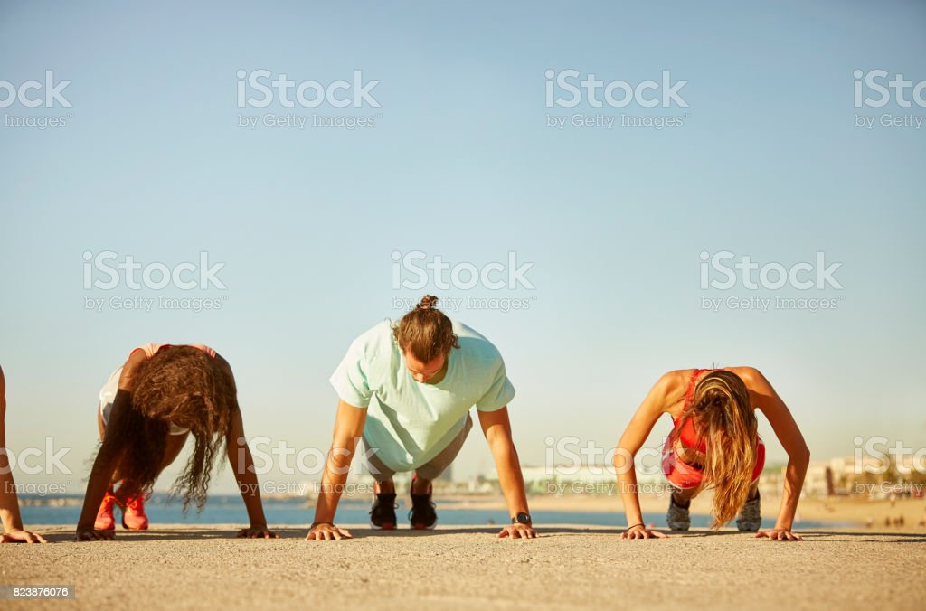 Friends doing push-ups on concrete against sky stock photo