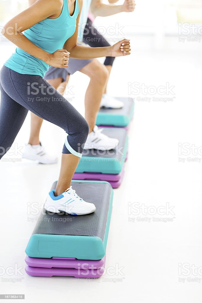 Friends Doing Step Aerobics In Health Club royalty-free stock photo