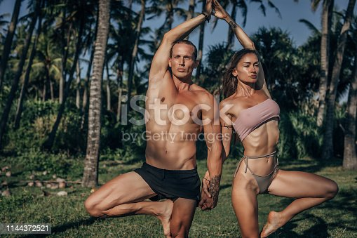 Two young man and woman doing yoga meditation and stretching exercises at beach