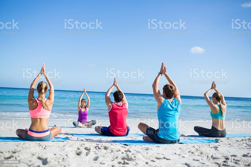 Friends doing yoga together with their teacher stock photo