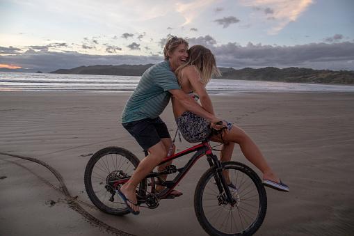 Friends double on mountain bike ride down sandy beach