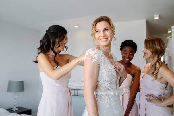 Friends dressing the bride for wedding stock photo