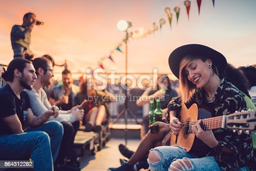 Group of friends enjoying a social gathering with guitar music on the rooftop