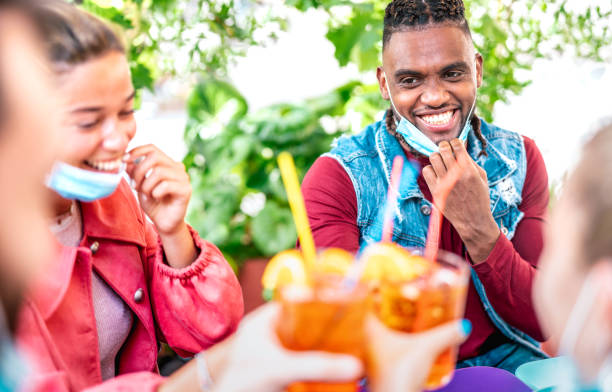 Friends drinking at cocktail bar with face masks - New normal friendship concept with happy people having fun together toasting drinks at open air pub - Bright filter with focus on afroamerican guy stock photo