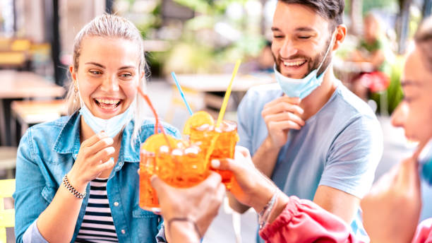 Friends drinking at cocktail bar with open face masks - New normal lifestyle concept with happy people having fun together toasting drinks at restaurant - Bright vivid filter with focus on left woman stock photo