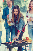 Friends drinking beer and barbecuing at a garden party