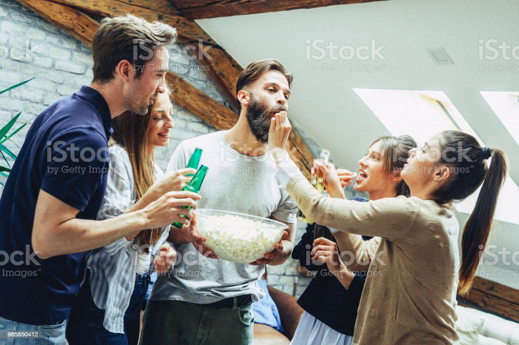 Vänner dricka öl och äta pop corn - Royaltyfri Alkohol Bildbanksbilder