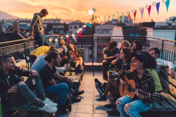 party-freunde, trinken bier und das gitarrenspiel auf dach - terrassen lichterketten stock-fotos und bilder