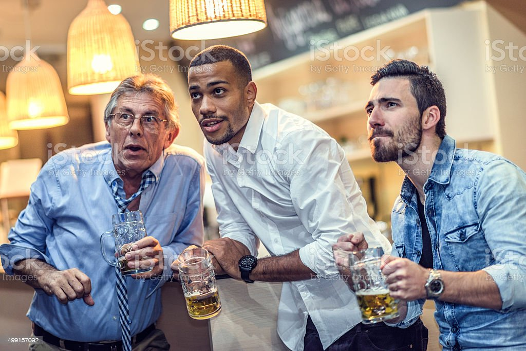 Friends drinking beer and watching a sports game stock photo