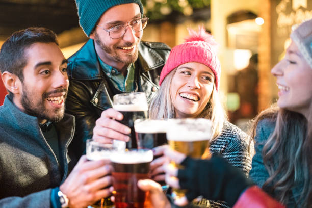 Friends drinking beer at brewery bar outdoor on winter time - Friendship concept with young people having fun together toasting at happy hour promotion - Focus on girl with pink hat - Warm neon filter stock photo