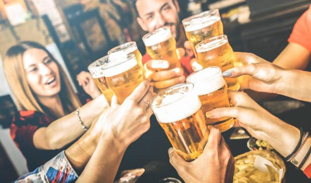 amis buvant la bière au restaurant de bar de brasserie le week-end-concept d'amitié avec les jeunes ayant l'amusement ensemble griller la pinte de bière sur l'happy hour au pub-focus sur le verre-filtre à contraste lumineux - café boisson photos et images de collection