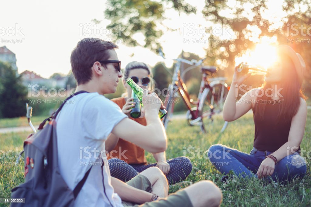 Friends drinking beer at sunset stock photo