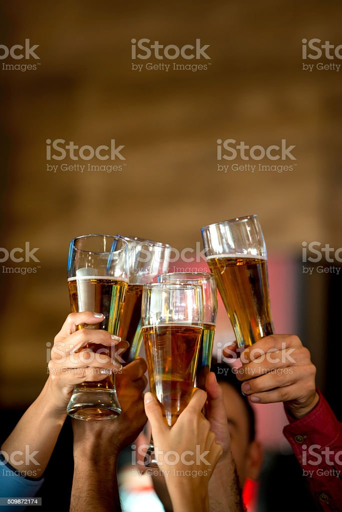 Friends drinking beer at the bar - foto de acervo