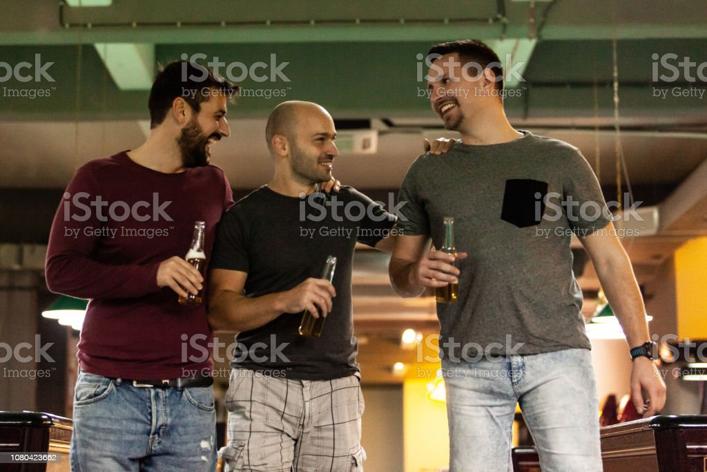Friends drinking beer in bowling alley stock photo