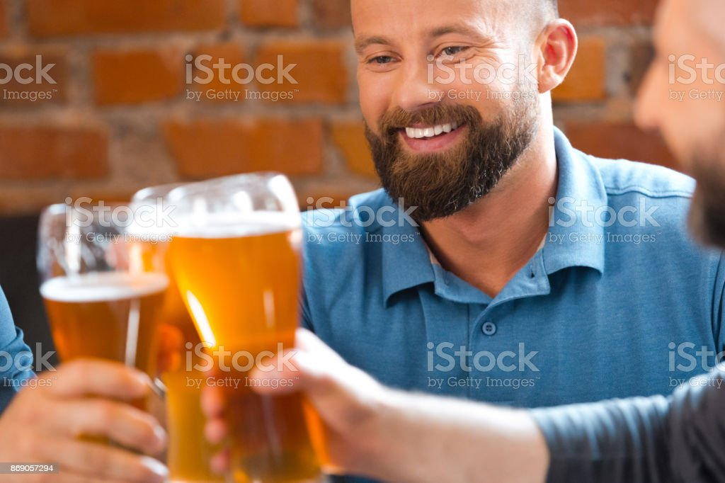 Friends drinking beer in the pub Friends drinking beer in the pub, toasting with beer glasses. 35-39 Years Stock Photo
