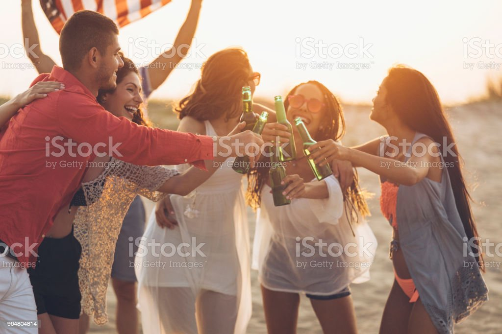 Friends drinking beer on beach and cheering royalty-free stock photo
