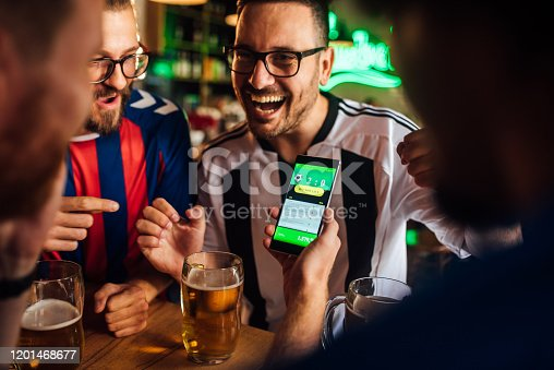 Soccer fans drinking beer at the pub and using mobile app for betting.