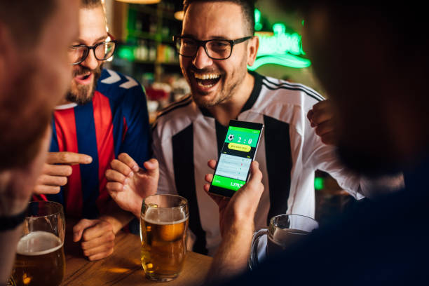 Friends drinking beer, watching soccer game and using mobile app for betting stock photo