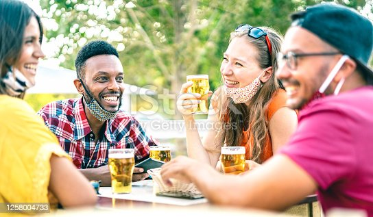 Friends drinking beer with opened face masks - New normal lifestyle concept with people having fun together talking on happy hour at brewery bar - Bright vivid filter with focus on afroamerican guy