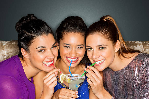 friends drinking cocktail together through straw at nightclub - margarita drink stock photos and pictures