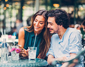 Young couple at sidewalk cafe text messaging