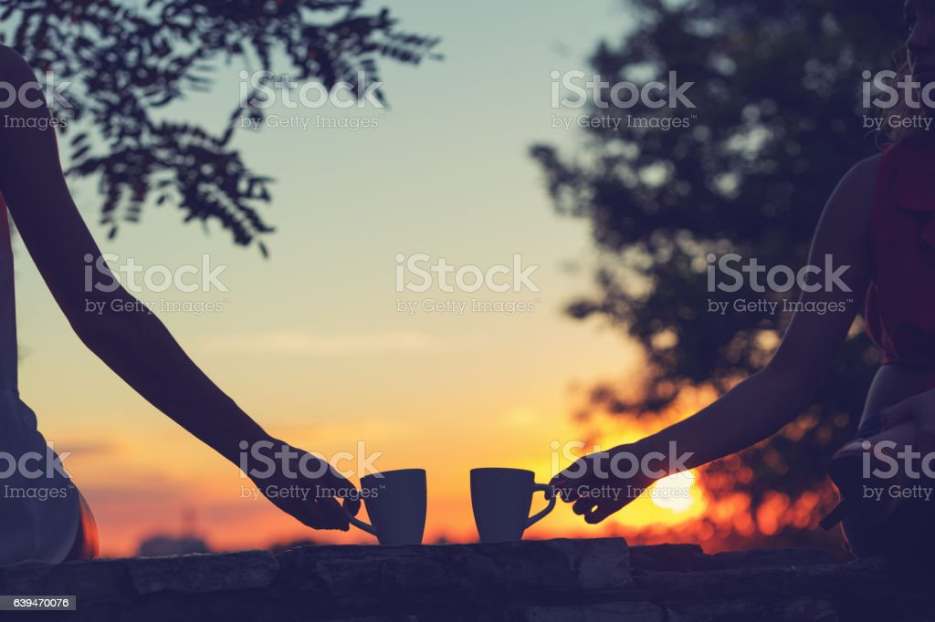 Amigos bebiendo café en la puesta de sol y el amanecer. - foto de stock