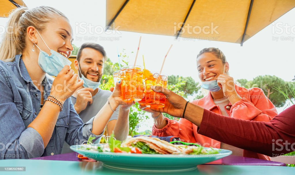 Friends drinking coktail and eating snack tapas in a restaurant bar outside in summer days with face mask on to be protected from coronavirus - Happy people cheering with spritz and having fun Lifestyle in coronavirus time Alcohol - Drink Stock Photo