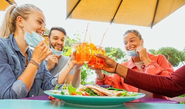 friends drinking coktail and eating snack tapas in a restaurant bar outside in summer days with face mask on to be protected from coronavirus - happy people cheering with spritz and having fun - covid restaurant imagens e fotografias de stock