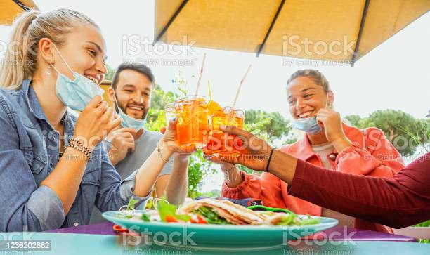 Friends Drinking Coktail And Eating Snack Tapas In A Restaurant Bar Outside In Summer Days With Face Mask On To Be Protected From Coronavirus Happy People Cheering With Spritz And Having Fun Stock Photo - Download Image Now