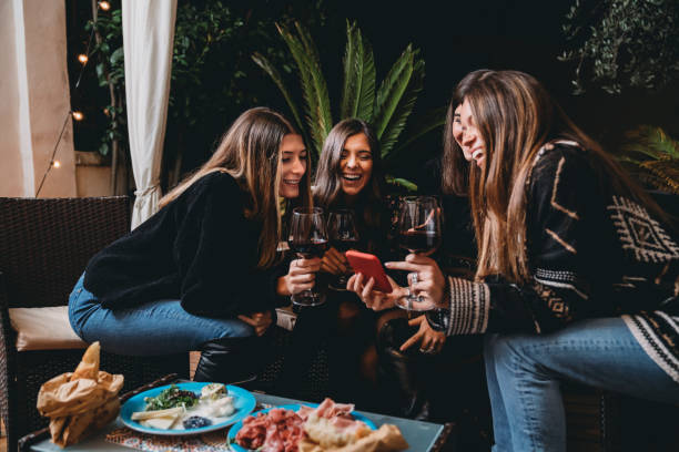 Friends drinking red wine and looking at a smartphone together stock photo