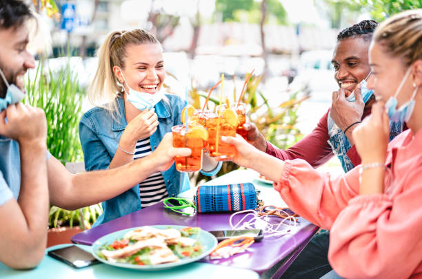 Friends drinking spritz at cocktail bar with face masks - New normal friendship concept with happy people having fun together toasting drinks at restaurant - Bright filter with focus on left woman stock photo