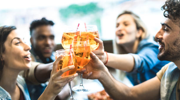 Friends drinking spritz at fashion cocktail bar restaurant - Friendship concept with young people having fun together toasting drinks on happy hour at pub - Focus on central glass - Teal orange filter stock photo