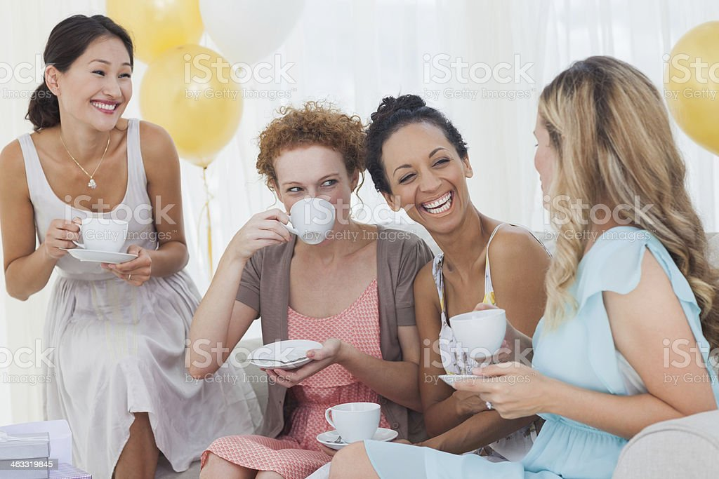 Friends drinking tea and chatting at a party stock photo