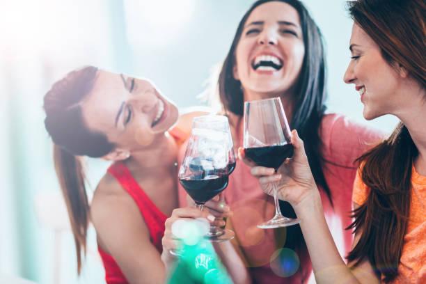 Friends drinking wine in restaurant, having fun - foto de acervo