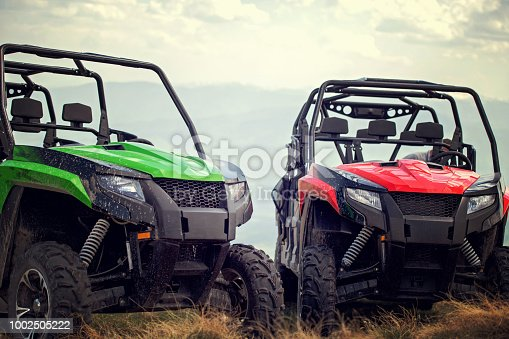 Friends driving off-road with quad bike or ATV and UTV vehicles.