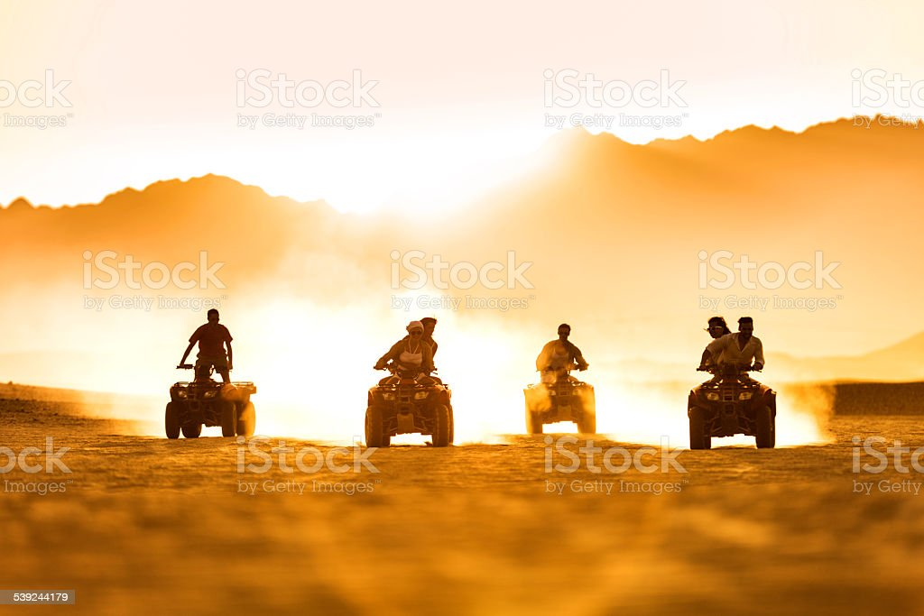 Friends driving quad bikes at sunset. stock photo